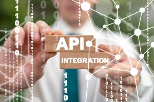 api integration concept. hands holding 2 wooden blocks. one says API the other Integration
